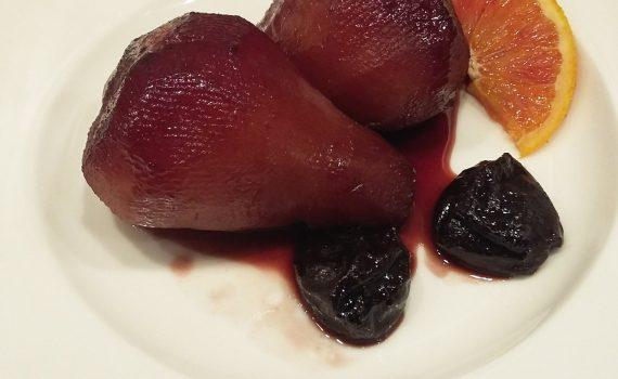 pere al vino servite con prugne e fetta di arancia